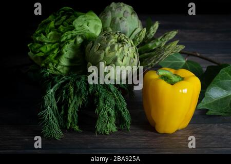 Artichokes, yellow pepper, asparagus, herbs, salt and pepper on wooden table - Stock Photo