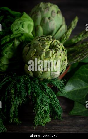 Artichokes, herbs, salt and pepper on wooden table - Stock Photo