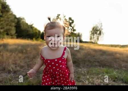 Little girl is playing in nature. Baby girl have fun in the park, running barefoot on the green grass. Fun and carefree childhood.