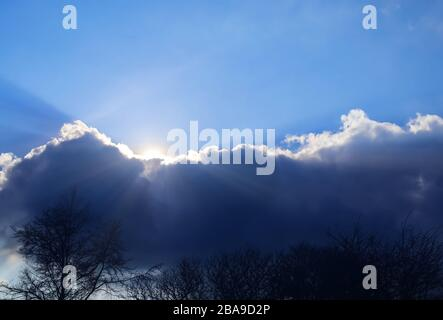 Beautiful sunlight beams through a stunning cloudscape in the sky - Stock Photo