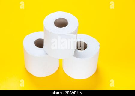 Three rolls of toilet paper on a yellow background - Stock Photo