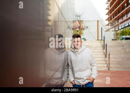 Portrait of young male with hands on pocket leaning on wall outdoors