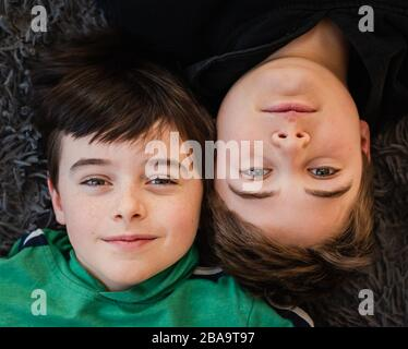Looking down at the faces of two boys laying beside each other. - Stock Photo