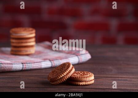 Sandwich biscuits, Cream biscuits, Cookies with cream filling on wooden table - Stock Photo
