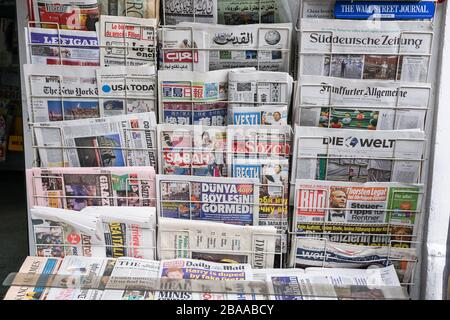 Rack with British and international newspapers outside newsagent's shop in London, UK - Stock Photo