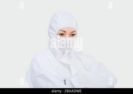 Female doctor in protective suit and face mask. Paramedic upset woman on white background. - Stock Photo
