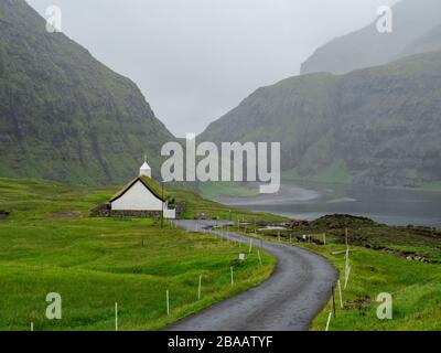 Faroe Islands, Streymoy, Saksun. View on Saksun's church and valley. White building with grass roof standing out of the green fields. - Stock Photo