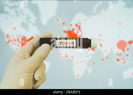 Hand in a glove holds flask with the inscription coronavirus on the background of map with infections. - Stock Photo