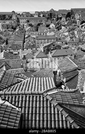 View of the clay tile rooftops of Old Town Dubrovnik, Croatia with the Mediterranean Sea in the background. - Stock Photo