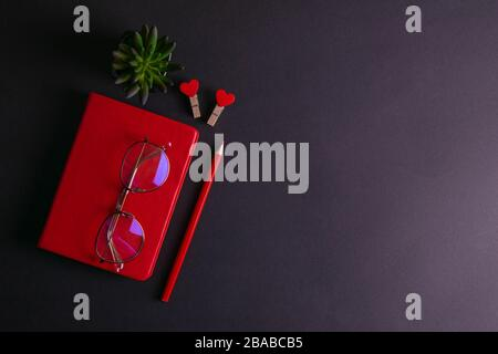 The red notebook stands on a black background, on the notebook there are glasses and next to the notebook, a flower, two clothespins in the shape of - Stock Photo