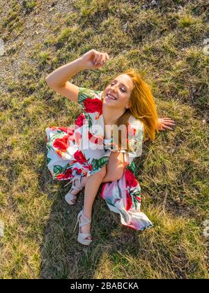 Teen girl in very colorful flowery pattern patterned fabric long dress with slit side cut view from above looking up upwards smiling - Stock Photo