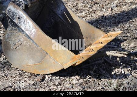 The rusty metal bucket, or shovel, of an excavator is detached from the machine and sitting on the ground, which is covered in dirty leaves and debris - Stock Photo