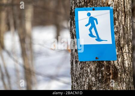 A blue-and-white sign features an illustration of a stick figure wearing snowshoes. This trail marker indicates a trail suitable for snowshoeing. - Stock Photo