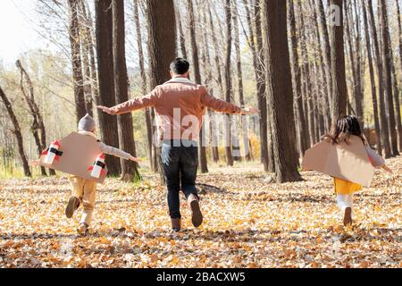 The happy children and his father in the outdoor running back - Stock Photo