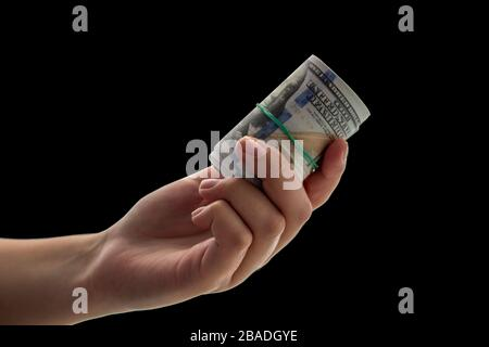 Twisted 100 dollars bills in hand on a black background. Concept for business or coronavirus crisis. Costs of quarantine savings through unemployment. - Stock Photo