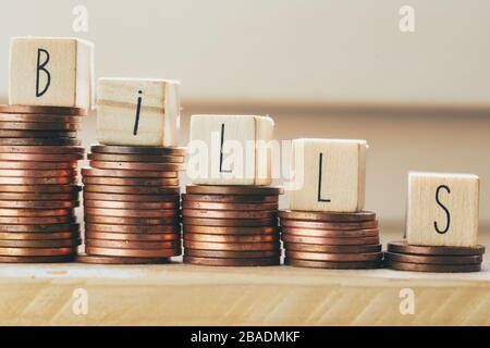 Wooden blocks with the word bills and pile of coins, money climbing stairs Payment of taxes and of debt to the state. Concept of financial crisis and - Stock Photo