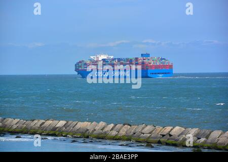 Rotterdam, The Netherlands-September 2019; wide angle view of a large containership arriving in Rotterdam port with the large breakwater concrete ston - Stock Photo