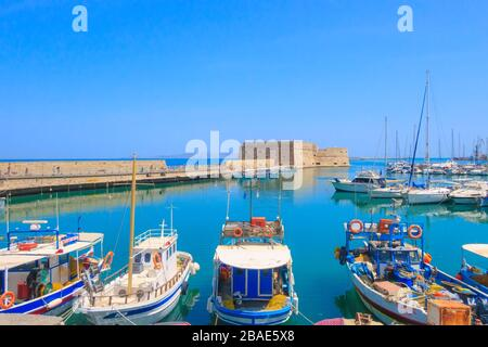 Heraklion, Greece - April 27, 2019: Crete island old harbor with fishing boats and Venetian fortress of Rocca al Mare - Stock Photo
