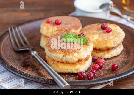 Homemade pancakes with cottage cheese on a wooden lantern with black currants and cranberries. Breakfast for the whole family. Healthy vegan food conc