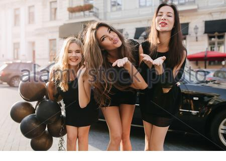 Attractive girls with bright make-up sending air kisses while dancing on the street. Outdoor portrait of glamorous fair-haired lady carrying balloons and having fun with friends. - Stock Photo