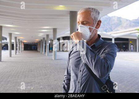 Middle aged man wearing Coronavirus Covid19 mask coughing