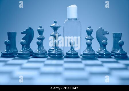 Coronavirus concept image chess pieces and hand sanitizer on chessboard illustrating global struggle against novel covid-19 outbreak. - Stock Photo
