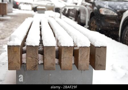 a bench made of wood under the first snow on the street - Stock Photo