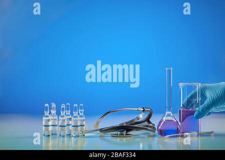 Hand in disposable glove holding beaker with purple chemical reagent. Six ampoules with liquid, syringe, medical flask and phonendoscope, blue backgro Stock Photo