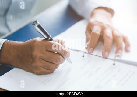 closeup elder hand writing paper working with ball pen in office desk. - Stock Photo