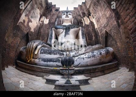 Giant statue of Buddha call Phra Achana in Wat Si Chum at Grey overcast sky in Sukhothai Historical Park, Thailand - Stock Photo