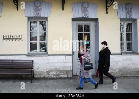 Moscow, Russia. 27th Mar, 2020. MOSCOW, RUSSIA - MARCH 27, 2020: Women wearing protective face masks pass by the Fahrenheit restaurant at Tverskoi Boulevard during the ongoing COVID-19 pandemic. According to a decree by Moscow Mayor Sergei Sobyanin, from 28 March to 5 April 2020, all restaurants, cafes, bars, and other eating establishments must shut down, except for delivery and take-away services with no customers visiting their premises. Mikhail Tereshchenko/TASS Credit: ITAR-TASS News Agency/Alamy Live News - Stock Photo