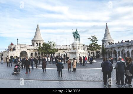 Budapest, Hungary - Nov 6, 2019: Fishermans Bastion in the Hungarian city. One of the best-known monuments in town, built in Neo-Romanesque style. Tourists sightseeing. St. Stephen equestrian statue. - Stock Photo