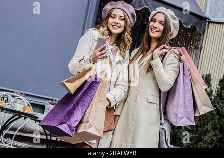Happy shopaholic friends. Low-angle view of two beautiful french women looking to camera and smiling while standing outdoors. Women with shopping bags - Stock Photo