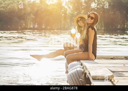 Young and carefree girls. Two young and attractive women in swimsuits drinking lemonade and smiling while having fun on wooden pier. - Stock Photo