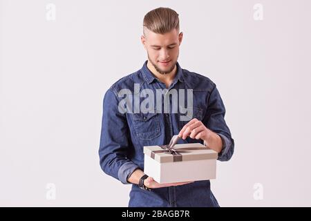Studio shot of bearded hipster man tying gift box and smiling while isolated on white background. Young handsome man in denim shirt opening birthday p - Stock Photo