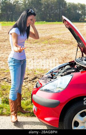 Junge Frau hat eine Autopanne, Motorschaden,  MR: Yes - Stock Photo