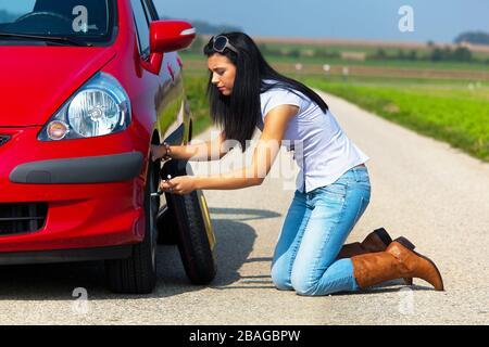 Junge Frau hat eine Autopanne und wechselt einen Reifen, Reifenwechsel, MR: Yes - Stock Photo