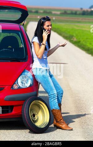Junge Frau hat eine Autopanne, Reifenwechsel, telefoniert um Hilfe, MR: Yes - Stock Photo