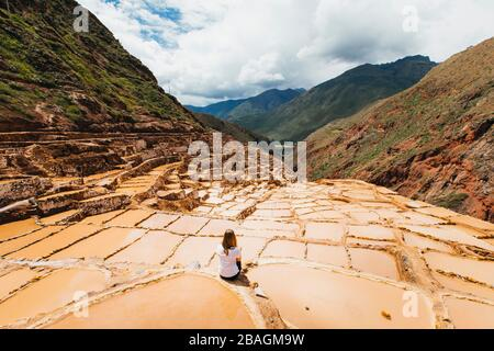 Young woman is sitting near the famous salt mines in Peru