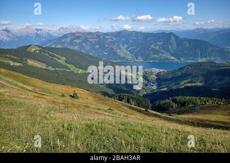 View across meadow and forest, from Schmittenhöhe, Austria.  Looking down to Lake Zell and town of Zell am See beyond. - Stock Photo