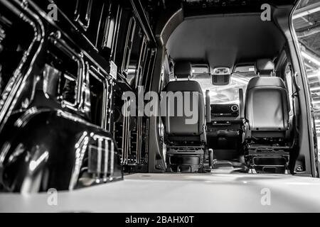 The black popular useful compact diesel minivan with empty cargo compartment and open doors is ready for loading commercial goods for next delivery - Stock Photo