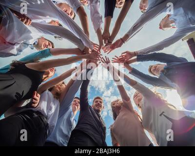 A friendly company of friends join hands as a sign of joint business. - Stock Photo
