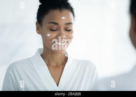 African woman applied facial cream doing skincare procedures at home