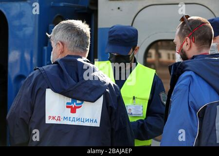 MOSCOW, RUSSIA - MARCH 28, 2020: Paramedics in face masks are seen at Moscow's Kiyevsky Railway Station after the arrival of a special train which took Russian citizens from Kiev, Ukraine. Russia and Ukraine have agreed a deal to briefly resume train connection between the two countries to repatriate their citizens in connection with the pandemic of the novel coronavirus (COVID-19). The special train with Russian citizens left Kiev on 27 March. On its return journey, the train will take Ukrainian citizens to Kiev. Vladimir Gerdo/TASS - Stock Photo