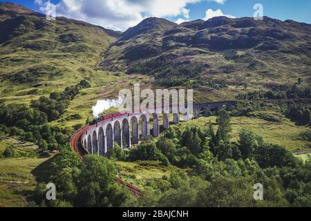 Glenfinnan Railway Viaduct in Scotland with the Jacobite steam train passing over. - Stock Photo