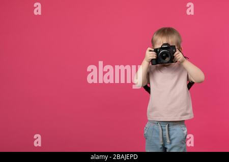 SAINT-PETERSBURG, RUSSIA - MARCH 22, 2020: A child boy stands and holds in his hands a Canon 70d camera with a lens with an EF 50mm 1.4 mount and take - Stock Photo