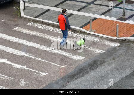 Male wearing protective face mask holds a dog on leash at an empty city street, due to coronavirus traffic restrictions in Thessaloniki, Greece. - Stock Photo