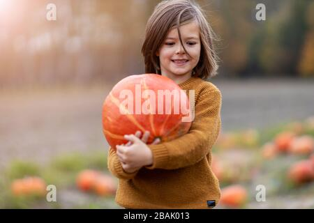 Cute little boy having fun in a pumpkin patch