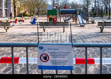 Deserted public children's playground closed and obstructed with tape due to the 2020 COVID-19 / coronavirus / corona virus pandemic - Stock Photo
