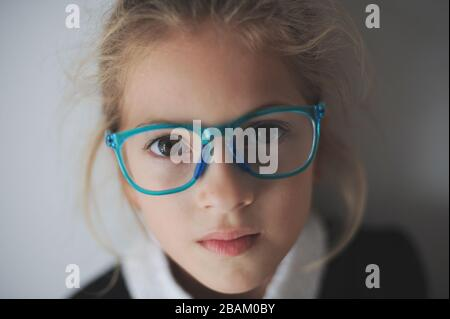 beautiful little sad girl in blue glasses - Stock Photo